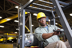 African American worker operating forklift