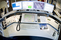 A dispatcher's desk with multiple screens and a phone