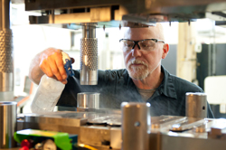 A toolmaker spraying on machinery