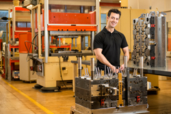 A professional toolmaker looking at camera and smiling