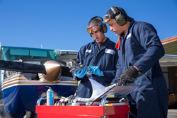 Two Male Airplaine Mechanics Working on a Small Plane