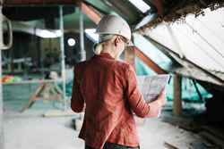 Female Architect Looking Over Blueprints