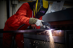 Plasma Operator Using a Cutter in Steel Fabrication Factory