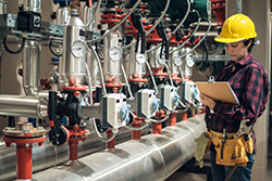 A Female System Engineer in a Boiler Room Taking Readings