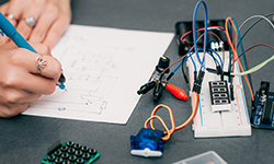 Electrical Designer working on wiring diagram drawing with breadboard