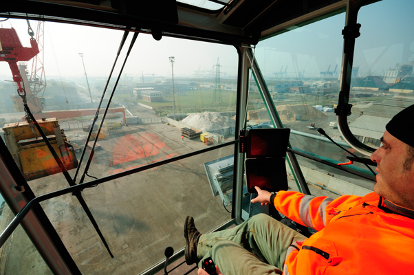 Men in orange operating a crane at the docks