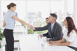 A woman shaking hands with the interviewer after a successful job interview