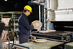 A quality control specialist inspecting metal discs