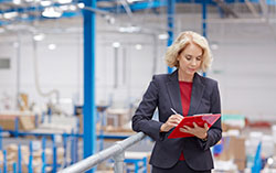 Inventory Control Woman with Clipboard in Warehouse