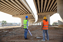 Civil Designers Standing Beneath a Bridge Under Construction