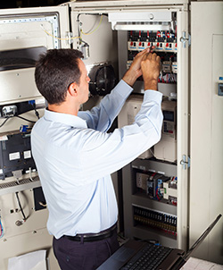 Electrical PLC Programmer Working on a Computerized Machine