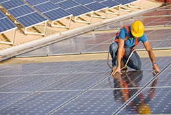 Solar Engineer Fixing a Solar Panel on a Rooftop