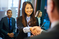 A Happy Young Woman Shaking Hands After a Successful Job Interview at a Staffing Agency