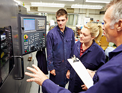 Engineer Interns being supervised by a CNC operator